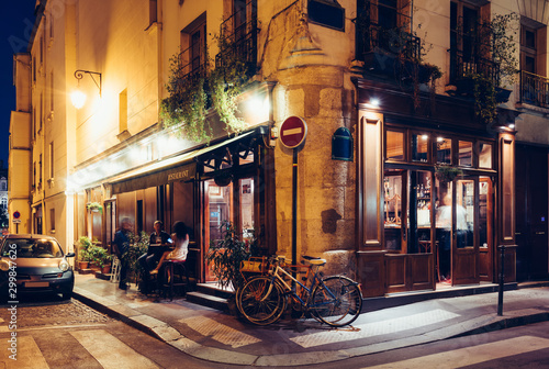 Foto auf Leinwand Fahrrad Night view of cozy street with tables of cafe and old bicycle in Paris, France