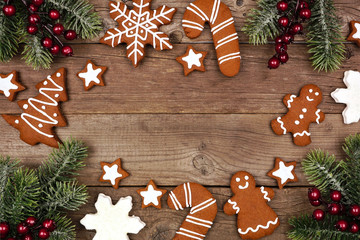 Christmas frame of gingerbread cookies and tree branches. Top view on a rustic wood background with copy space.