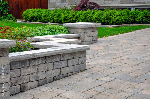 Fotomural  A seat wall with pillars and natural stone coping helps define a tumbled paver driveway and is a beautiful landscaping feature