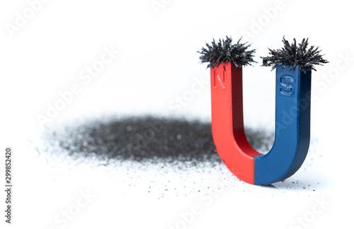 Photo Horseshoe magnet attracting iron powder on white background