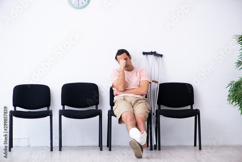 Young injured man waiting for his turn in hospital hall Wallpaper Mural