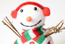 Closeup Of Adorable Snowman Wearing A Red White And Green Scarf And Earmuffs