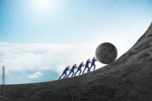 Fototapeta Team of people pushing stone uphill