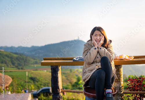 Fototapeta  Asian women sit happily in the morning, sip coffee and eat bread atop the hill in the morning happily