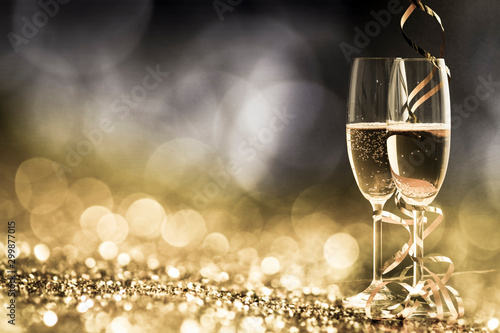 Poster de jardin Alcool two champagne glasses with ribbons against holiday lights and fireworks - New Year celebrations