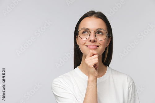 Fototapeta Portrait of young woman with dreamy cheerful expression, thinking, wearing glasses, isolated on gray background with copy space obraz na płótnie