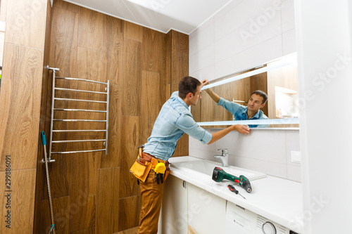 Man installing a mirror on wall in his renewed bathroom Wallpaper Mural