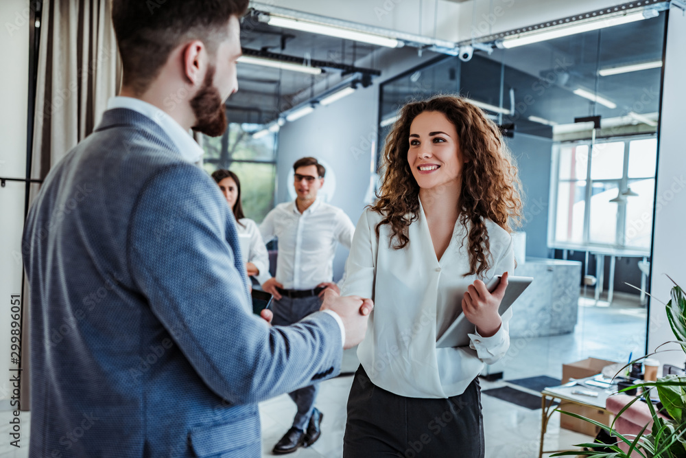 Fototapeta Man and woman are shaking hands in office. Collaborative teamwork.Business professionals