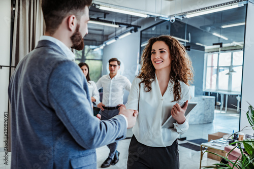 Photographie Man and woman are shaking hands in office