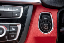 Close-up, Isolated Image Of An Engine Start Stop Button Seen On The Dashboard Of A German Manufactured Sports Car, Also Showing Its Part Red Leather.