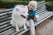 Happy elderly Caucasian lady palming nice dog in park