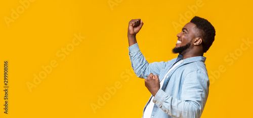 Slika na platnu Happy black guy raising fists in the air, celebrating success