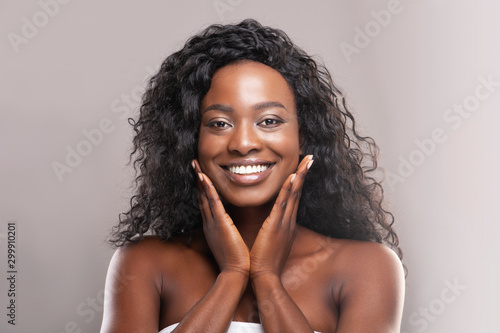 Valokuvatapetti Beautiful african american woman touching her smooth skin on cheeks