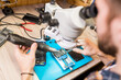 Hands of repairman with electric handtool looking in microscope during work