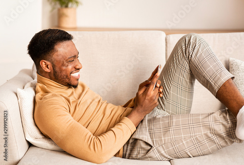Relaxed Guy Using Smartphone Lying On Sofa At Home Fototapet