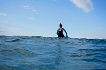 A Girl Surfer Paddles A Longbo...