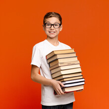 Smart Teenage Boy In Glasses Holding Stack Of Books