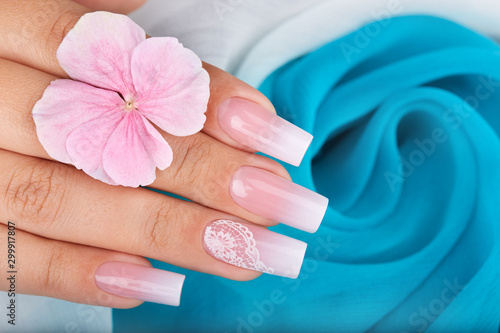 фотография Hand with long artificial manicured nails with ombre gradient design in pink and