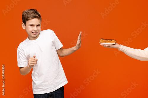 Fényképezés  Teen boy feeling disgust, refusing chocolate donut