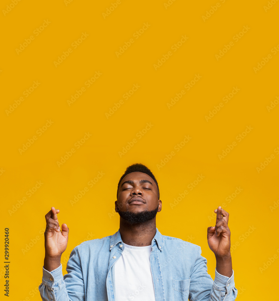 Fototapety, obrazy: Concentrated african american man crossing fingers for luck