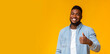 Happy african guy gesturing thumb up on yellow background