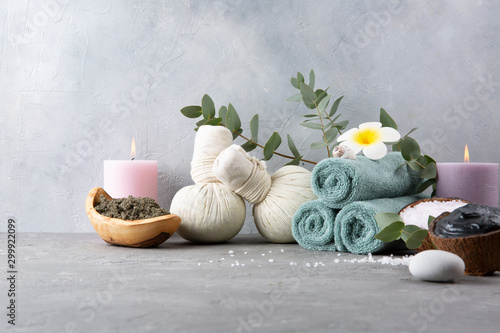 Beautiful spa and relax concept. Green tea scrub, dead sea mud, cotton pouches with herbs for massage, sea stones, eucalyptus and other Spa accessories on grey table.