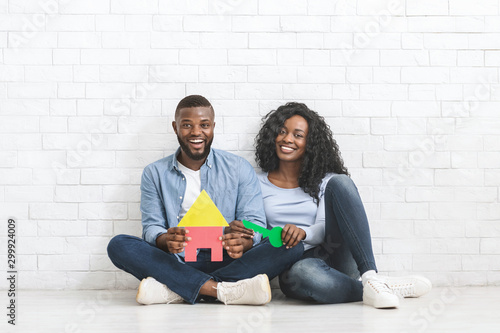 Fotomural  African couple holding colorful plastic house and key