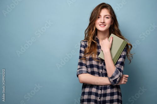 Obraz A young girl in a plaid shirt stands on a blue background with a book and looks joyfully at the camera. - fototapety do salonu