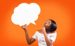 Leinwandbild Motiv Young Black Woman Holding Speech Bubble Standing, Orange Background, Mockup