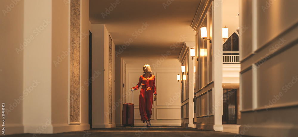 Fototapety, obrazy: Full-length portrait of gorgeous lady with blonde hair wearing red jumpsuit walking along the hall in hotel with a suitcase. Business trip concept. Horizontal shot. Front view