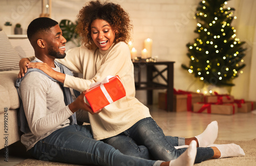 Fotomural  Handsome man surprising girl with Christmas present