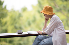 Middle Aged Woman Sitting On The Bench And Reading A Book In The Park