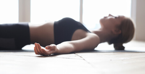 Yoga girl laying on sport mat, relaxing after exercising