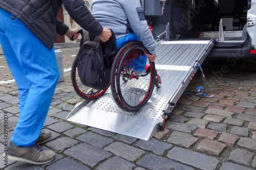 Foto Assistant helping disabled person on wheelchair with transport using accessible