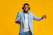 Cheerful guy in headphones listening music on smartphone and dancing