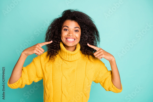 Photo of amazing dark skin curly lady indicating fingers on perfect condition teeth advertising dentist wear yellow knitted pullover isolated blue teal color background - 299944625