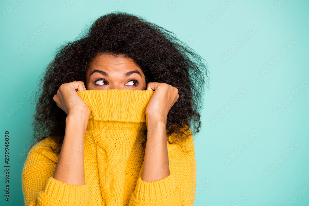 Fototapeta Close up photo of funny dark skin wavy lady hiding half facial expression with collar looking empty space wear yellow knitted pullover isolated teal color background