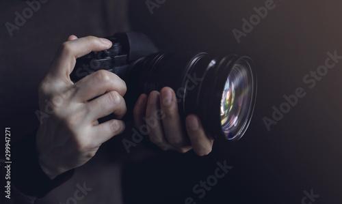 Obraz Young Photographer Woman using Camera to Taking Photo. Dark Tone. Selective Focus on Hand - fototapety do salonu