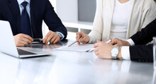 Business People Discussing Contract Working Together At Meeting At The Glass Desk In Modern Office. Unknown Businessman And Woman With Colleagues Or Lawyers At Negotiation. Teamwork And Partnership