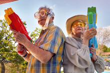 Modern Senior Couple Have Fun Playing With  Water Gun.