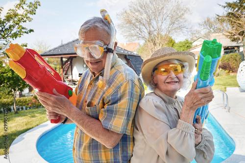 Modern Senior people have fun playing with water gun.