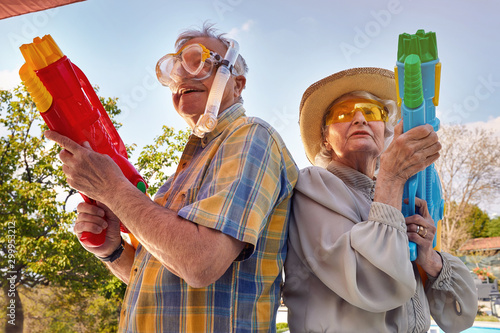 Obraz Modern Senior couple have fun playing with  water gun. - fototapety do salonu