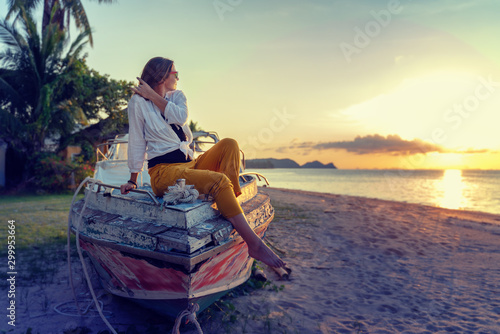 Foto auf Gartenposter Sansibar Girl in a white shirt sitting on an old deryavyanoy boat on the beach and watching the sunset, relax in the tropics, vacation and travel concept