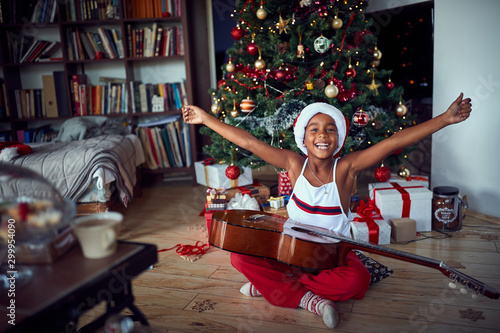 happy girl sitting on floor  with guitar present at home on Christmas Fototapete