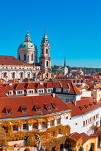 Roofs Of Old Prague With Church Of St. Nicolas On A Bright Autumn Day With Blue Sky