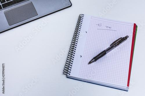 Obraz na plátne  Libreta con lista sobre mesa blanca de oficina con ordenador portátil