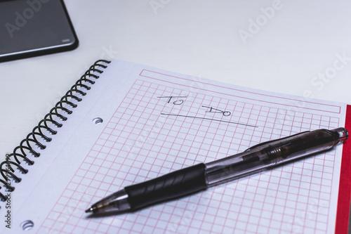Fototapeta  libreta y bolígrafo sobre mesa blanca con ordenador portátil
