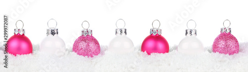 Fotobehang Europa Christmas border of shiny pink and white baubles resting in snow isolated a white background