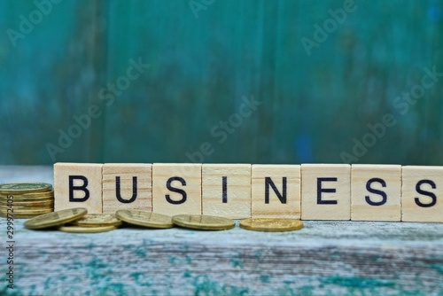 Fotografie, Obraz  business word made of wooden letters and yellow coins on a gray table