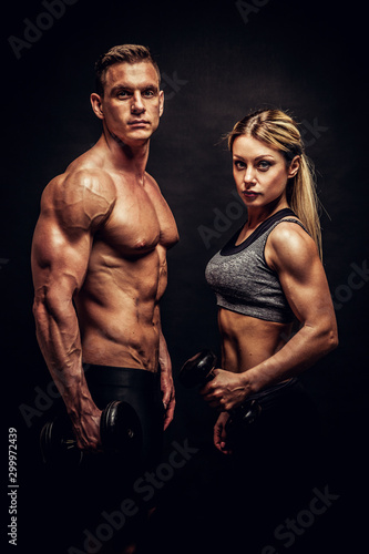 Fotografía  Sporty young couple posing on black background